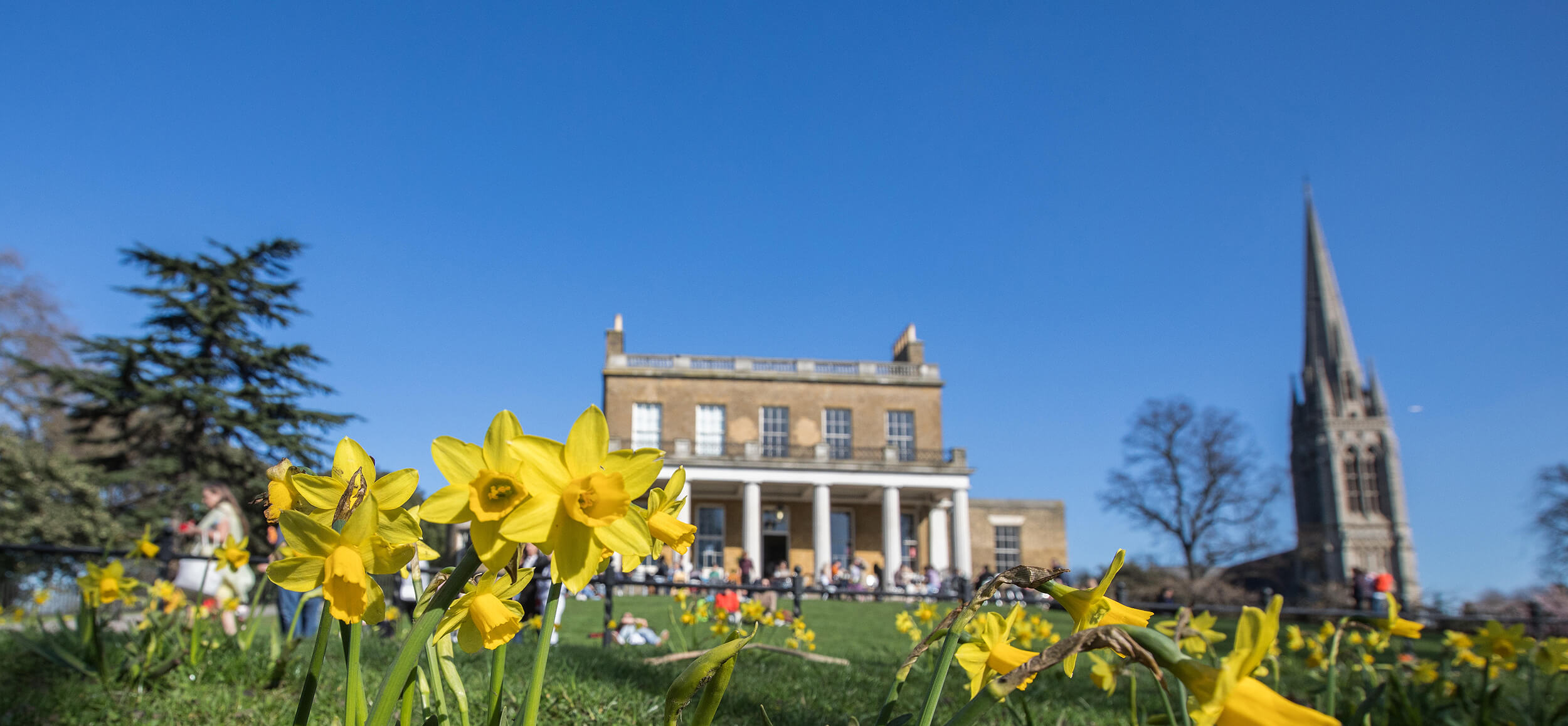 Photo of local landmark - Clissold House - with blue sky and daffodils